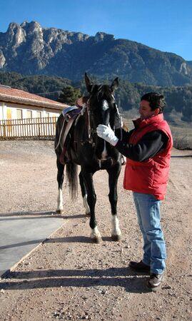 Uomo accarezza un cavallo prima di montarlo