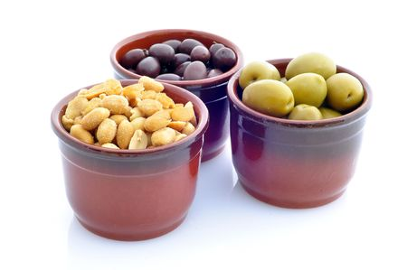 three containers with olives and peanuts on a white background Standard-Bild