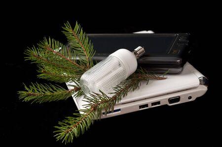 netbooks: netbooks and energy saving light bulb on black background Stock Photo