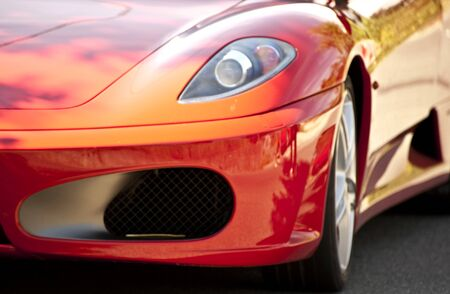 Detail of a red sports car on the road