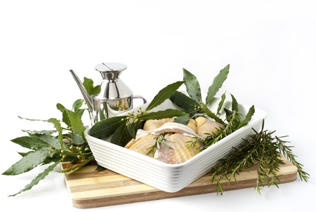 guinea fowl stuffed with bay leaves in a ceramic baking dish