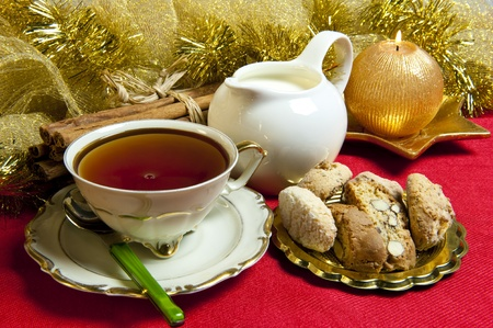 tea and cookies with Christmas decorations on red background