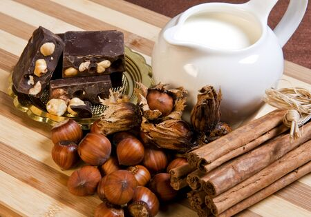 nougat chocolate, nuts, milk and cinnamon on bamboo cutting board