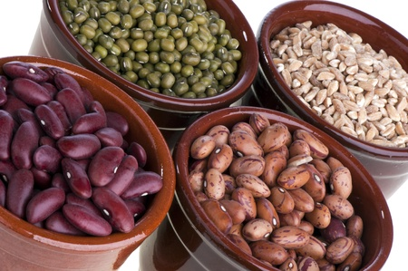 green beans: terraccota containers with three different types of beans and barley  Stock Photo