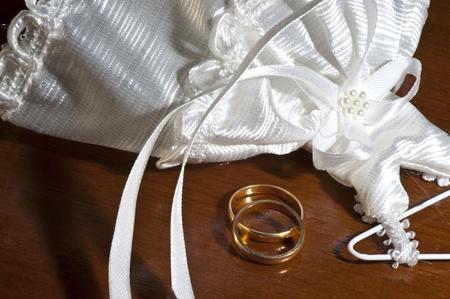 wedding favors: wedding favors and wedding rings on a dark wood table Stock Photo