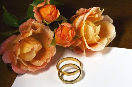 Wedding rings and roses on a dark background