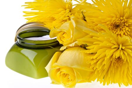 Yellow flowers and body lotion on a white background photo