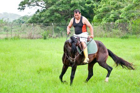 Men on horseback in the rain on a farm in Ecuador photo