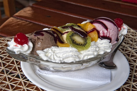 a portion of a banana split with fresh fruit toppings photo