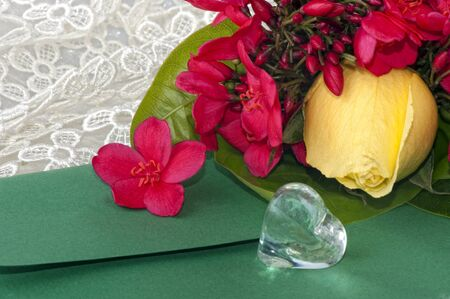 Jar with crystal heart-shaped yellow rose and flowers photo