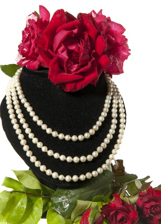 necklace and red roses on a white background photo
