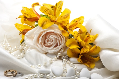 roses and wedding rings on white background photo