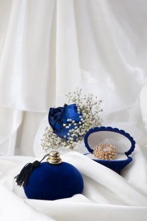 a  blue roses and wedding rings on white background photo