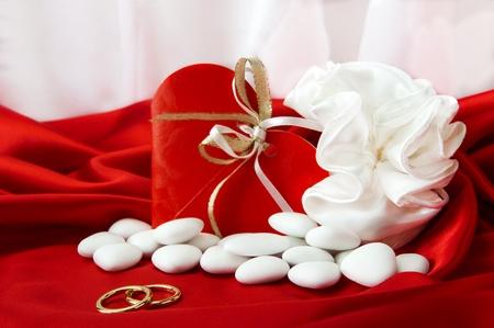 wedding favors:  wedding rings and wedding favors on  elegant fabric background Stock Photo