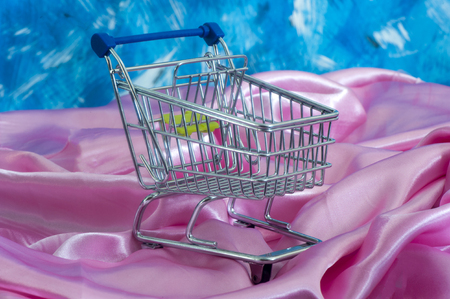 mamma: a shopping cart shopping cart to decorate the table on fabric background Stock Photo