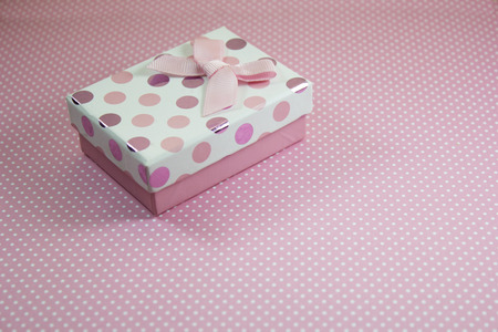 polka dots background: Gift box on pink polka dots background. Stock Photo