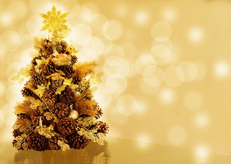 wealth: Christmas tree made of pine cones on golden bokeh background.