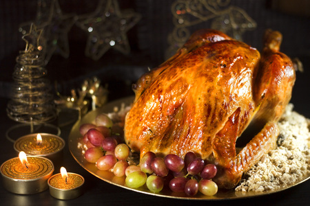 golden christmas: Roasted turkey on table set for Christmas with candles on dark background. Stock Photo