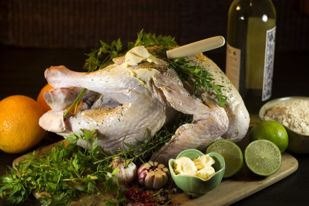 poultry: Raw turkey on wooden board with herbs lime butter and garlic.