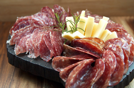 appetizers: Sliced ??salami and cheese on wooden board. Appetizers. Stock Photo