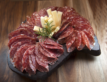 sliced: Sliced ??salami and cheese on wooden board. Overview. Stock Photo