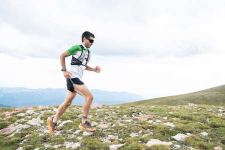 Athlete Runner Runs Rocks In Mountain. Sport Concept