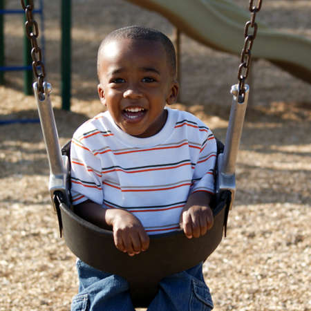 Happy little boy at the the parking swinging and laughing Stock Photo - 9728463