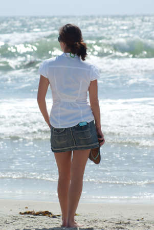 A young woman at the beach staring off into the ocean 版權商用圖片