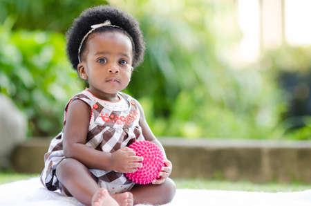 Cute baby afro-américaine séance jouer à l'extérieur avec un ballon rose Banque d'images - 34295719