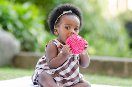 6 12 months: Cute African American baby sitting outdoors putting a ball to her mouth Stock Photo
