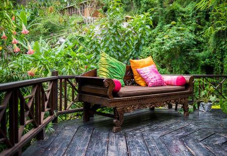clima tropical: Muebles de patio al aire libre con cojines de varios colores en la madera dura con follaje exuberante fondo Foto de archivo