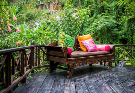 furniture: Outdoor patio furniture with multi color pillows on hardwood with lush foliage background