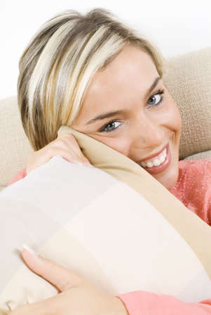 portrait of a pretty blond female wearing evening pink gown sitting on sofa with braids and arming a pillow Stock Photo - 781232