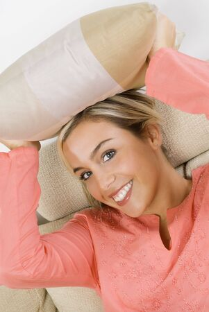 portrait of a pretty blond female wearing evening pink gown sitting on sofa with braids and arming a pillow photo