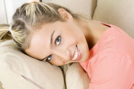 portrait of a pretty blond female wearing evening pink gown sitting on sofa and playing with hair photo