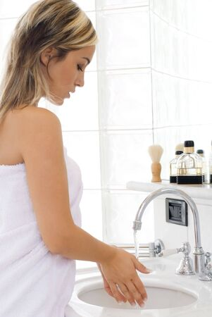 portrait of beautiful blond woman doing daily morning routines in front of the mirror