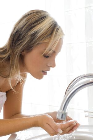 portret van mooie blonde vrouw doet de dagelijkse routines' s morgens voor de spiegel