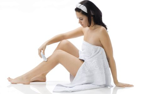 cute and young brunette dressing white towel shaving her legs photo