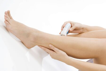nice closeup of cute and young girl dressing white towel and shaving her legs photo