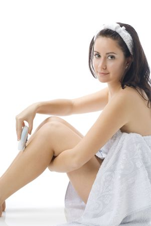 cute and young brunette dressing white towel shaving her legs