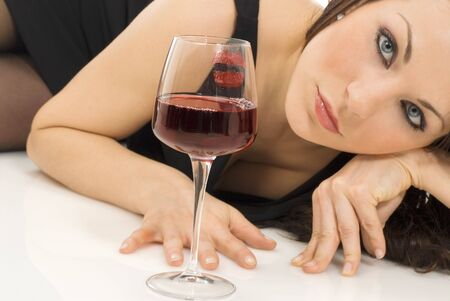 a sensual portreait of a cute and young brunette in a black dress with a glass of  italian red wine photo