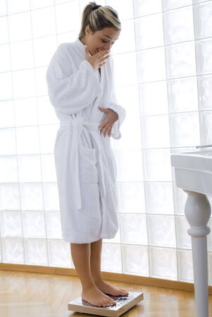 weight control: young blond woman wearing a white bathrobe doing weight control in her bathroom Stock Photo