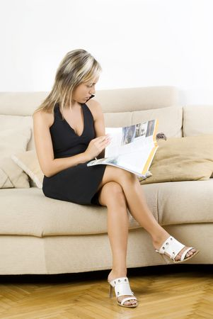 cute and blond girl in black dress reading a magazine and sitting on beige sofa photo