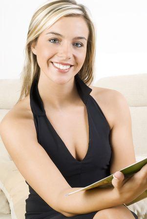 schattig en blond meisje in zwarte jurk het lezen van een magazine en zittend op beige sofa Stockfoto
