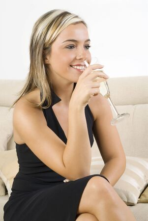 pretty woman in black dress drinking a glass of white wine sitting on sofa in her living room Stock Photo - 923411