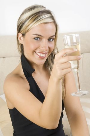 pretty woman in black dress drinking a glass of white wine sitting on sofa in her living room Stock Photo - 923415