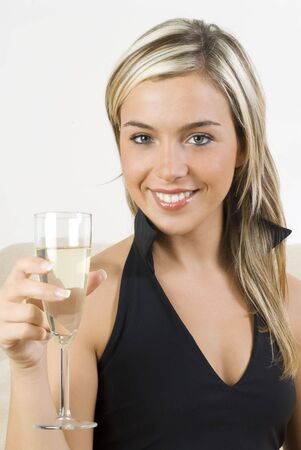pretty woman in black dress drinking a glass of white wine sitting on sofa in her living room Stock Photo