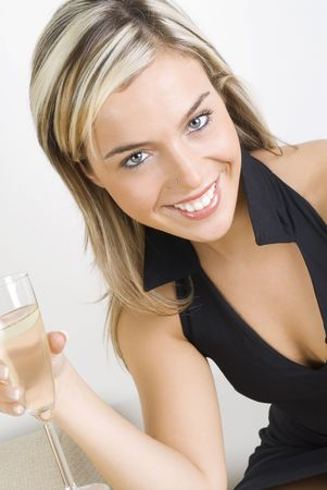 pretty woman in black dress drinking a glass of white wine sitting on sofa in her living room Stock Photo - 923416