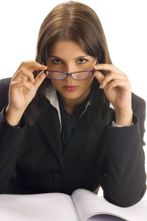 a young woman in black jacket and white shirt and a tie sitting down behind an office table and playing with glasses photo