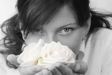 nice black and white portrait of a young woman with roses in her hands smelling and smiling with her fair eyes Stock Photo - 958318